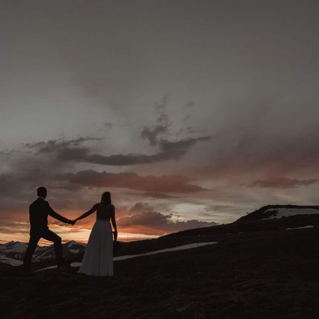 Estes Park Sunset Adventure Engagement Photographer. The couple is surrounded by the alpine lakes at 12000 feet among Rocky Mountains for their adventure session. Photos by Justyna E Butler Photography