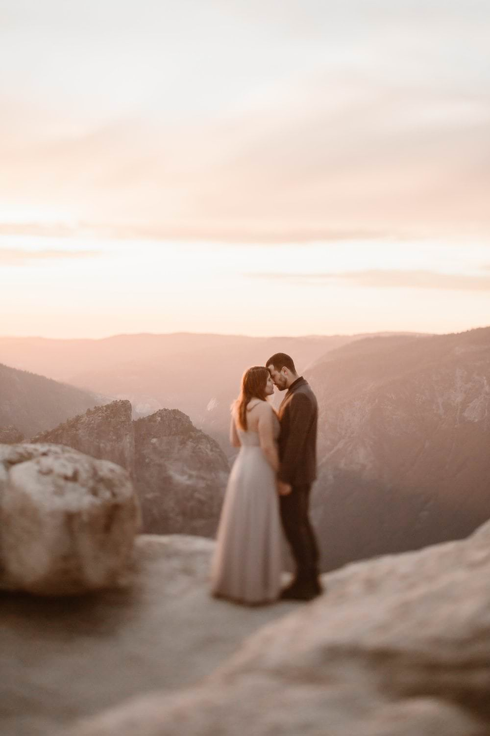 Yosemite National Park dreamy sunset at Taft Point. In the presence of sunset light Marie and her husband renewed vows at the most dreamiest places on Earth. The couples shared intimate moments while embracing each other, the adventure couple enjoyed an adventure hike among the dreamiest Colorado sunrise adventure hike. Photos captured by Justyna E Butler, Rocky Mountain Adventure Elopements and Intimate Weddings Photographer, Colorado Mountain Wedding Photographer, Destination Adventure Wedding Photographer