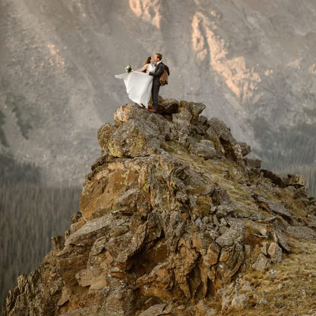 In the presence of fresh snowed capped alpine glaciers, in Colorado at Colorado Rockies Dana + Jeff enjoyed intimate moments while embracing each other, the adventure couple enjoyed an adventure hike among the dreamiest Colorado sunrise adventure hike. Photos captured by Justyna E Butler, Rocky Mountain Adventure Elopements and Intimate Weddings Photographer, Colorado Mountain Wedding Photographer