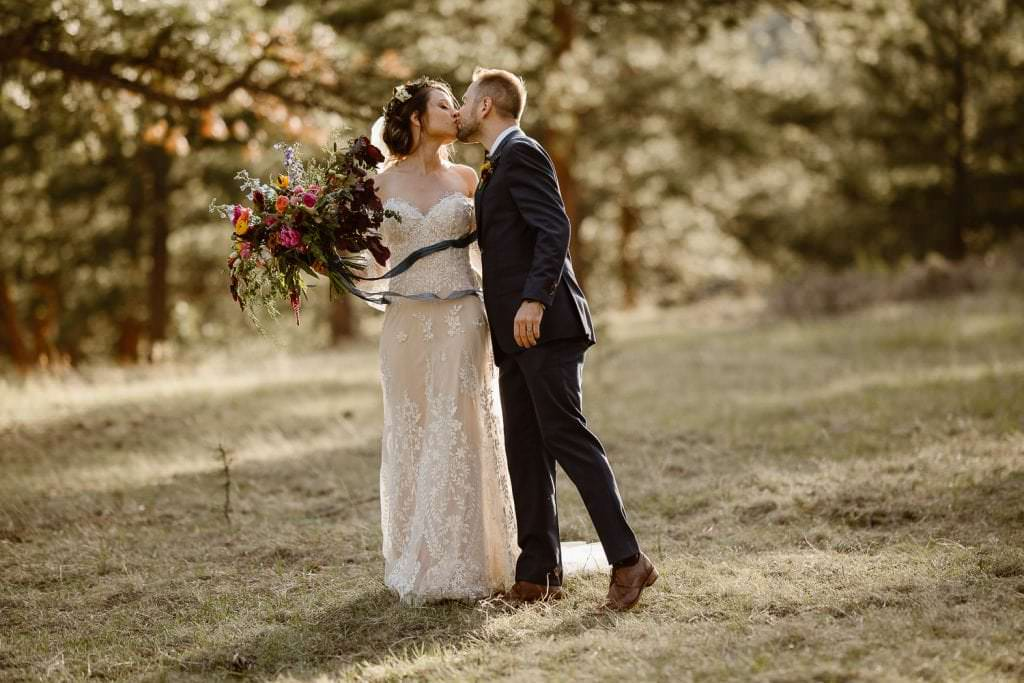 EMBRACING EACH OTHER DURING BRIDAL PHOTOS AT SUNSET AT DELLA TERRA MOUNTAIN CHATEAU COLORADO WEDDING | COLORADO WEDDING PHOTOGRAPHER | ESTES PARK COLORADO