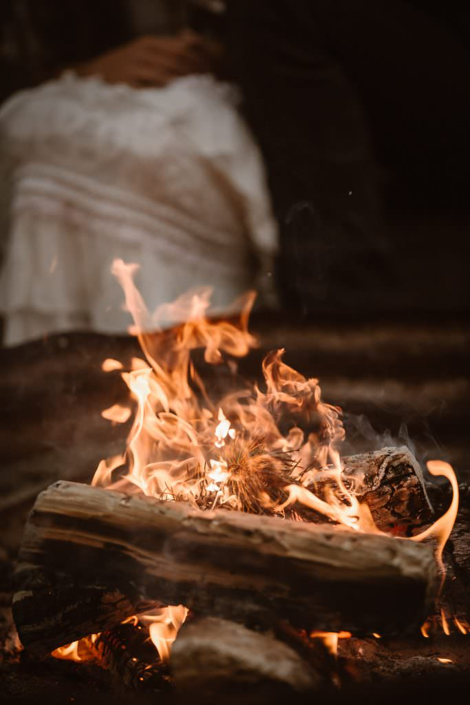 Bonfire at time at The adventure elopement couple reads the marriage license at Green River Adventure Backpacking Elopement Continental Divide Trail Adventure Elopement | Destination Adventure Wedding Photographer | Wyoming Wind River Range Adventure Elopement