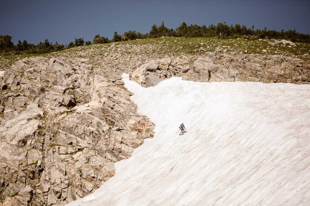 Skier is skiing in Colorado glacier at St Mary's Glacier for sun during summer.